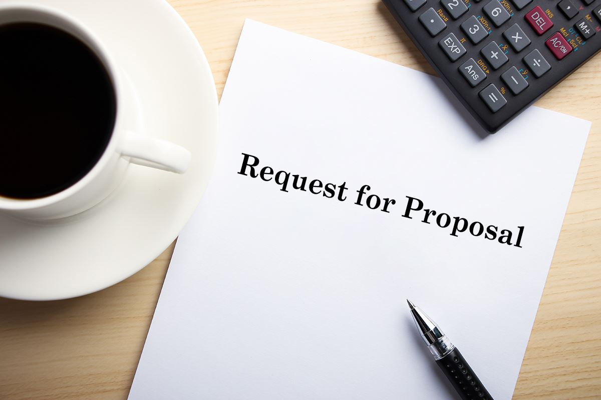 Request for Proposal packet on a table with coffee, keyboard, and pen