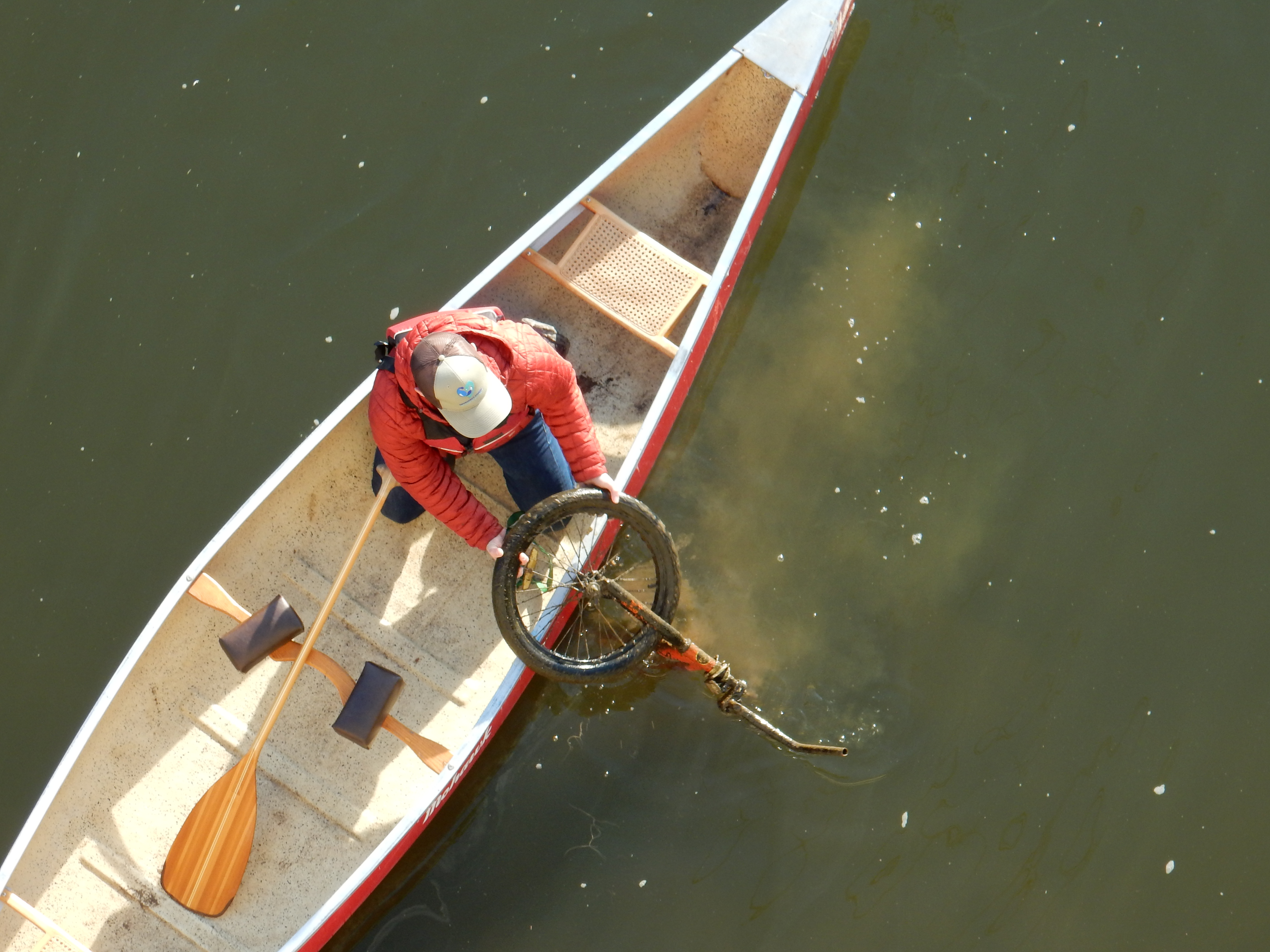 Birds-eye-view of a volunteer in a canoe pulling a bike from the river
